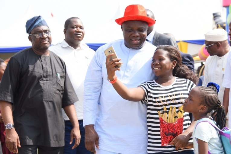 Two children taking a selfie with Lagos State Governor, Mr. Akinwunmi Ambode (2nd left), while Commissioner for Information & Strategy, Mr. Steve Ayorinde (left) and Senior Special Assistant to the Governor, Mr. Idowu Ajanaku (left behind), watch during the 2016 Children End of the Year party at the Lagos House, Ikeja, on Tuesday, December 20, 2016.