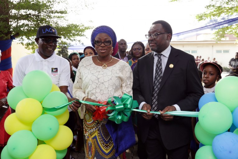 Wife of Lagos State Governor, Mrs. Bolanle Ambode (middle), being supported by Commissioner for Information & Strategy, Mr. Steve Ayorinde (right) and General Manager, Lagos Television, Mr. Deji Balogun, to cut the ribbon to signify the opening of the 2016 LTV Christmas Fair, at LTV Complex, Agidingbi, Ikeja, on Tuesday, December 6, 2016.