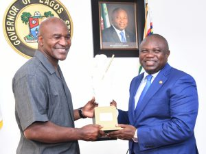 Lagos State Governor, Mr. Akinwunmi Ambode (right), presenting an Eyo plaque to  former Heavyweight Boxing Champion, Evander Holyfield during the courtesy visit by the former heavyweight boxing champion at the Lagos House, Ikeja, on Wednesday, May 24, 2017.