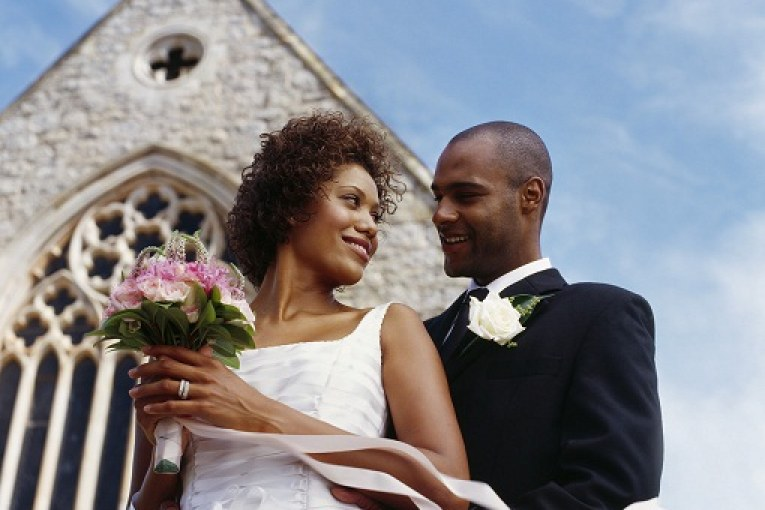 low angle view of a newlywed couple standing together outside a church --- Image by © Royalty-Free/Corbis