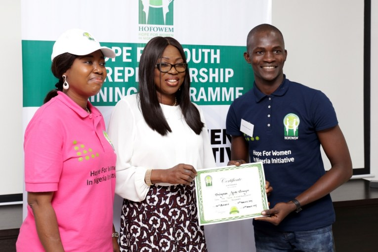 Founder, Hope for Women in Nigeria Initiative (HOFOWEM) and wife of Lagos State Governor, Mrs. Bolanle Ambode (middle),  presenting a Certificate of Attendance to one of the participants, Sulayman Afese Senayon (right) while the C.E.O, HOFOWEM, Ms. Oyefunke Adeleke (left), watches during the closing of a 2-day Hope for Youth Entrepreneurship Training Programme, organized by HOFOWEM to mark the 2017 International Youth Day, at the HOFOWEM's office in Oregun, Lagos on Tuesday, 15 August, 2017.