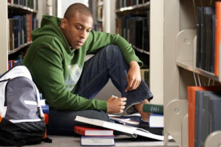Male college student studying on floor in library --- Image by © Ocean/Corbis