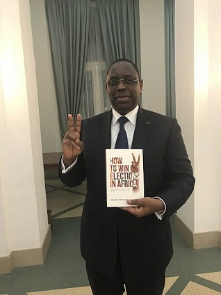 President Macky Sall poses with StateCraft Inc. flagship book, How to Win Elections in Africa