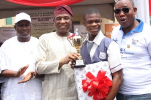 Representative of the Lagos State Governor and Secretary to the State Government (SSG), Mr. Tunji Bello (2nd left) presenting a trophy and prize to Master Abraham Tomiwa of Keke Senior High School, Agege, who emerged winner in the Agric Quiz competition during the 2016 World Food Day grand finale at the Johnson Agiri Agricultural Complex, Agege, on Sunday, October 16, 2016. With them are Commissioner for Agriculture, Hon. Toyin Suarau (left) and Special Adviser on Food Security, Mr. Ganiu Okanlawon Sanni (right).