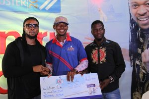 Flavour, brand ambassador for Life Continental Beer, and Akinola Josiah Olufemi, Assistant Brand Manager, Regional Mainstream Brands, NB Plc presenting a cheque of N250, 000 to Uzor Chibuzor, one of the lucky winners of the Life Progress Booster Show in Onitsha.